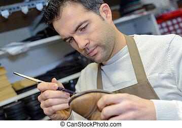 Cobbler repairing shoe