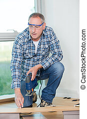 Man poised to cut wood with jigsaw