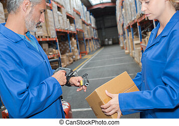 Man in warehouse wearing hand held scanner