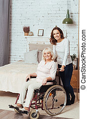 Joful woman holding wheelchair with her grandmother
