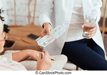 Pleasant caring nurse giving pills to an elderly woman
