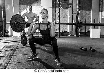 Strong well built woman lifting a barbell - Powerlifting...
