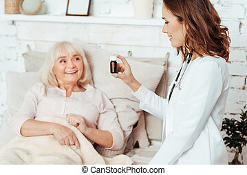 Kind doctor taking care of an old woman at home - One pill...
