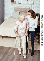 Positive loving woman helping disabled granny to walk with crutches