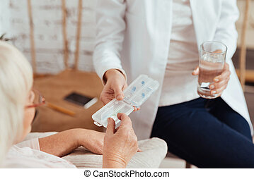 Professioanl nurse giving pills to elderly woman