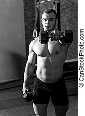 Well built muscular weightlifter holding dumbbells -...