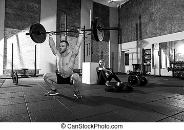 Powerful sporty man holding a barbell above his head - Great...
