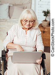 Pleasant elderly woman using laptop in the wheelchair