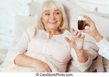 Professional doctor giving pills to an old woman