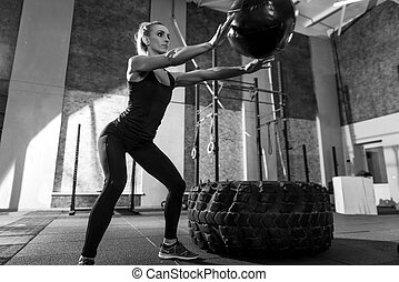 Sporty nice woman throwing a medicine ball - Active workout....