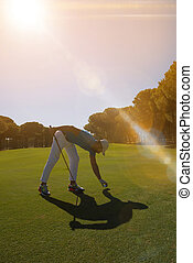golf player placing ball on tee.