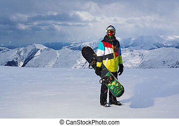 Snowboarder holding snowboard in hand standing in the...