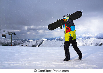 Snowboarder carries a snowboard in hand. Snowfall on the...