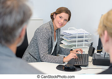 Lady typing while  in meeting with couple