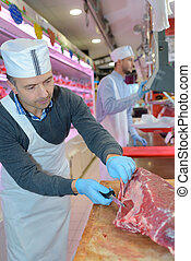 butcher teaching a young one how to sell meat