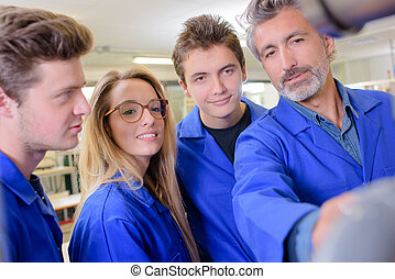Teacher with three students wearing blue jackets