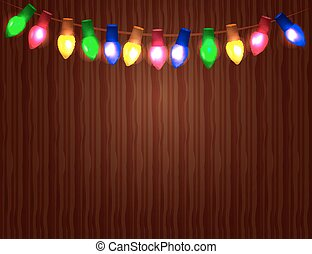 String of Color christmas light bulbs  on wooden background.