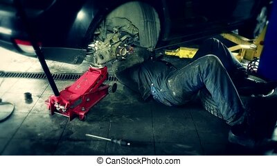 Male technician lying and working under car at repair garage...