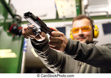 man at the shooting range. - The man at the shooting reloads...