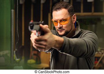 The man at the shooting range. - Shooting a gun at shooting...