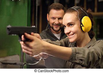 The woman at the shooting range. - The woman aiming a gun at...