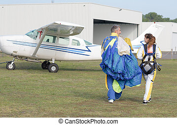 Man and woman walking with parachute at airfield