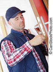 carpenter at lock installation into door