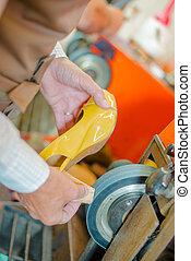 Cobbler grinding heel of shoe