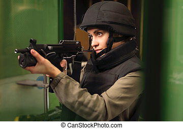 Woman shoots a rifle at the shooting range - Woman in vest...