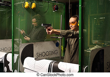 woman at the shooting range. - The woman aiming a gun at a...
