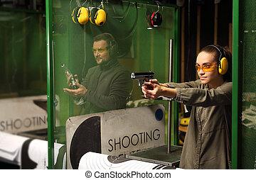 Woman shoots a gun at a shooting range. - The woman aiming a...