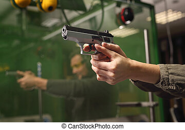 Learning to shoot a gun. - The woman aiming a gun at a...