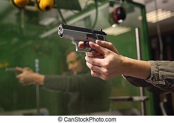 Learning to shoot a gun. - The woman aiming a gun at a...