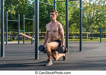 Young muscular fitness male model doing dumbbell lunge...