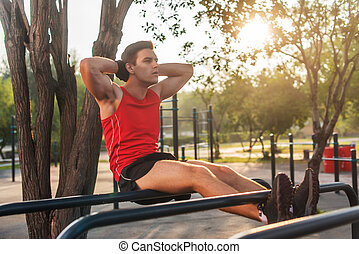Fit man doing sit ups on parallel bars outdoor fitness...