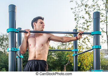 Young male athlete doing chin-up exercises in the park....