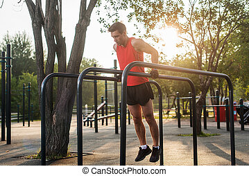 Fit man doing triceps dips on parallel bars at park...