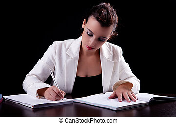 pretty woman in desk with papers, writing, isolated on black background. Studio shot.