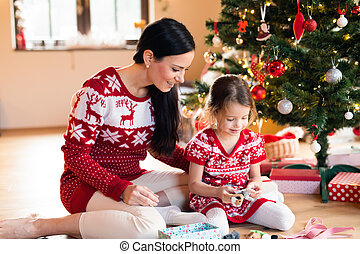 Young mother with daugter at Christmas tree at home. -...