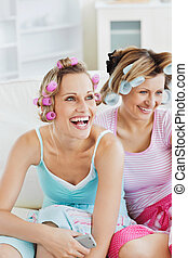 Female friends with hair rollers watching televison on the...