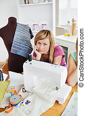 Depressed woman sewing clothes in the kitchen at home