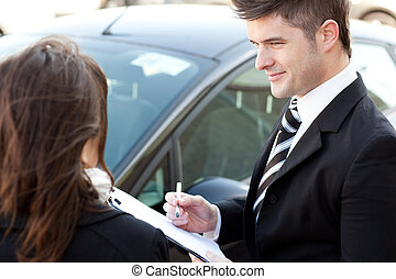 agent signing a contract with a female customer in a car...