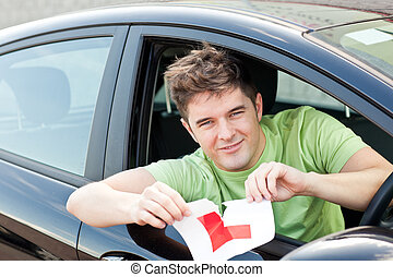 "Happy young man cutting a ""L"" sign sitting in his car"