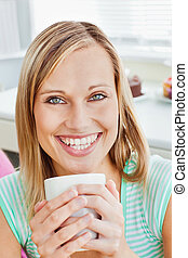 Glowing woman holding a cup of coffee at home in the kitchen