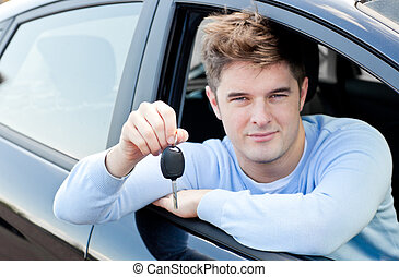 Charming young man holding a car sitting in his car smiling...