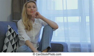 Woman poses on the couch at home - Gorgeous blond woman...