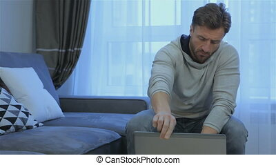 Man opens laptop at home - Attractive brunette man opening...