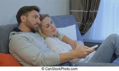 Couple watches TV at home