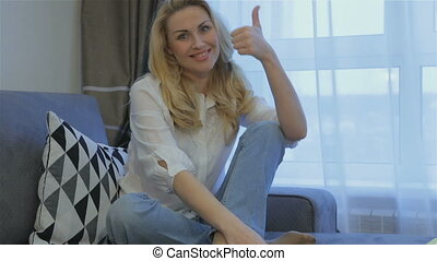Woman shows her thumb up at home
