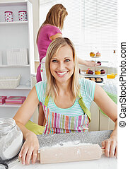 Beautiful caucasian woman baking together with her friend at...
